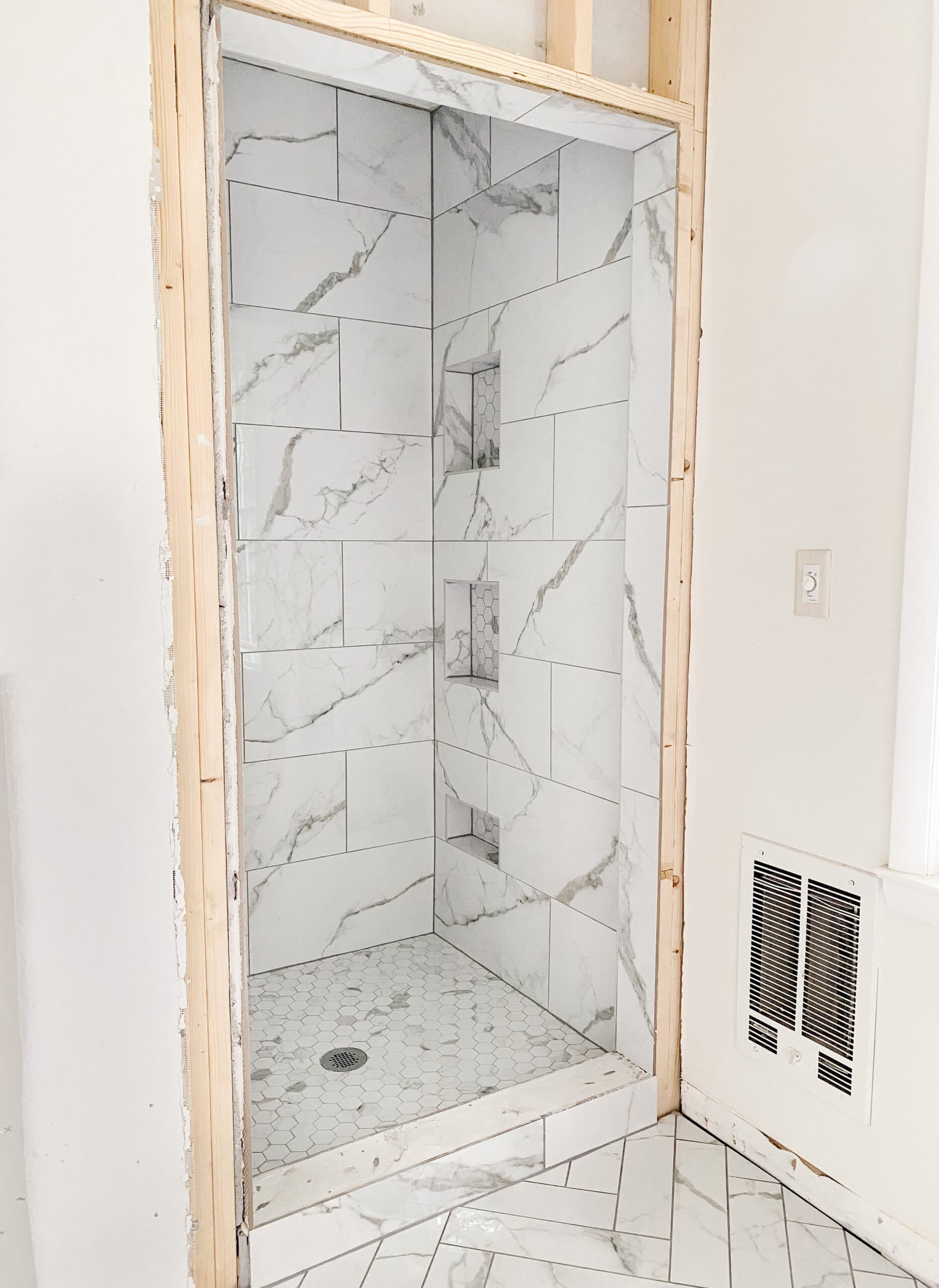 faux marble herringbone tile floor and faux marble tile shower with hexagon with gray grout