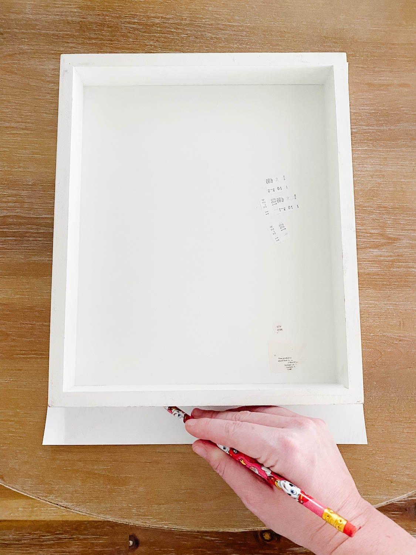 tracing a frame onto a vintage art print to trim