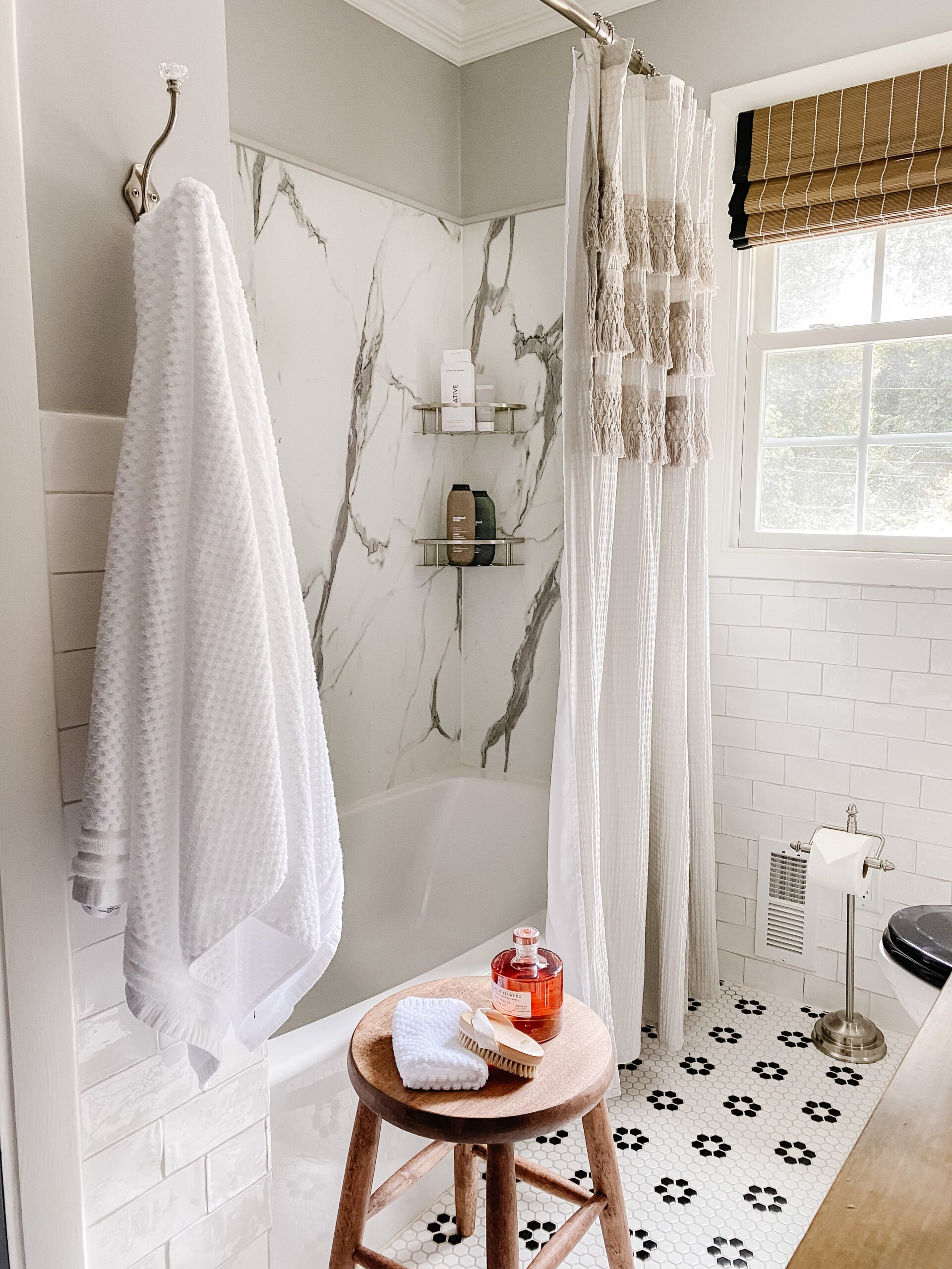 marble shower with black and white retro tile and gray shower curtain