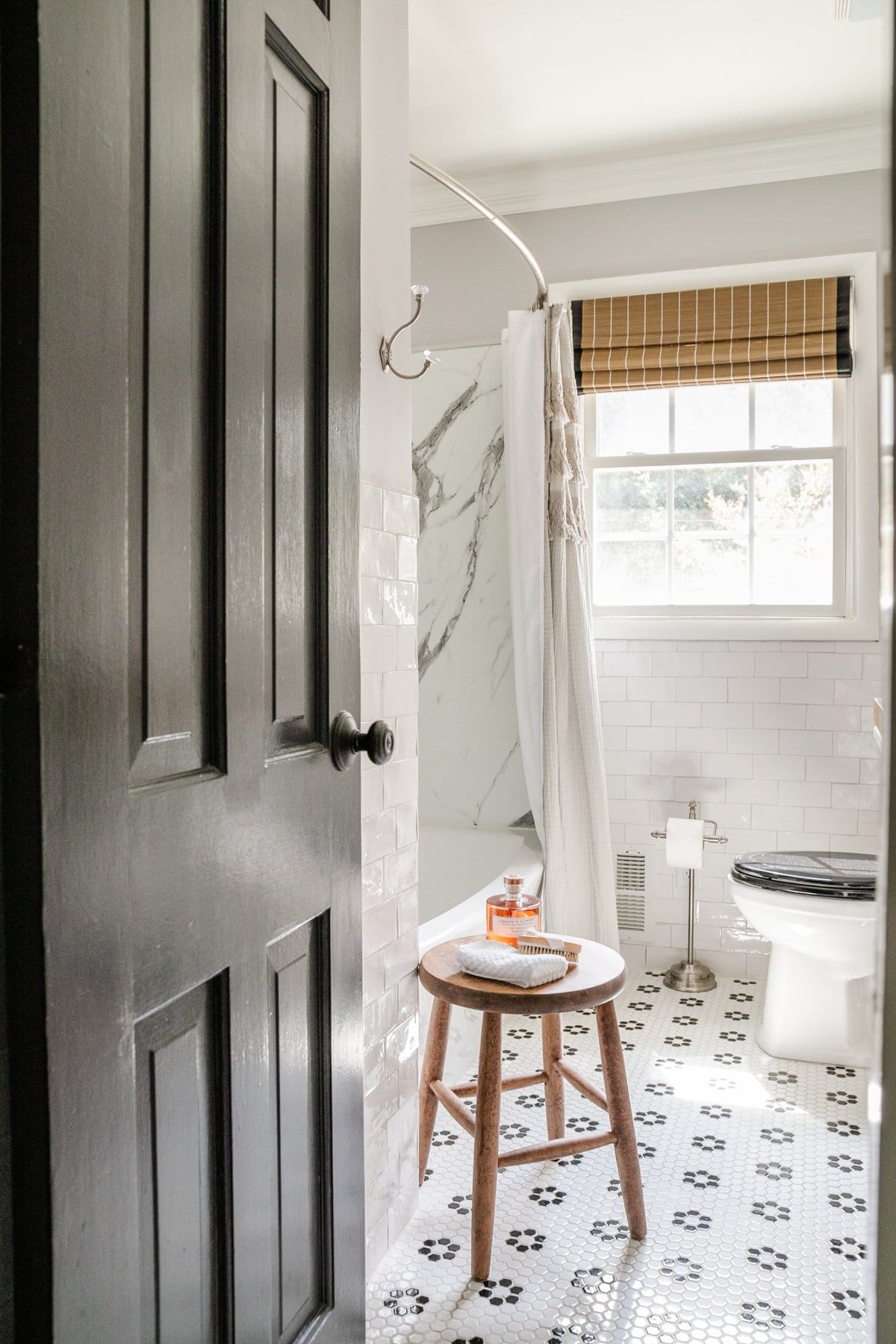 black and white bathroom decor with retro tile and stool beside the tub