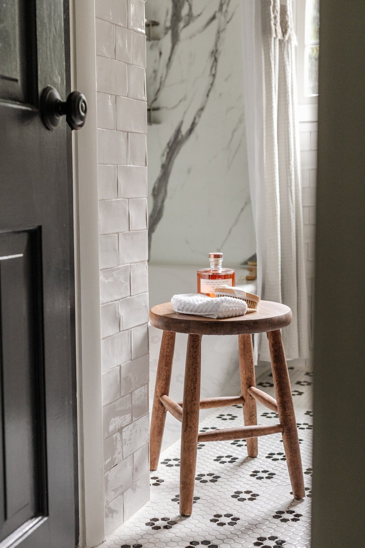 bathroom stool with toiletries and black and white bathroom tile