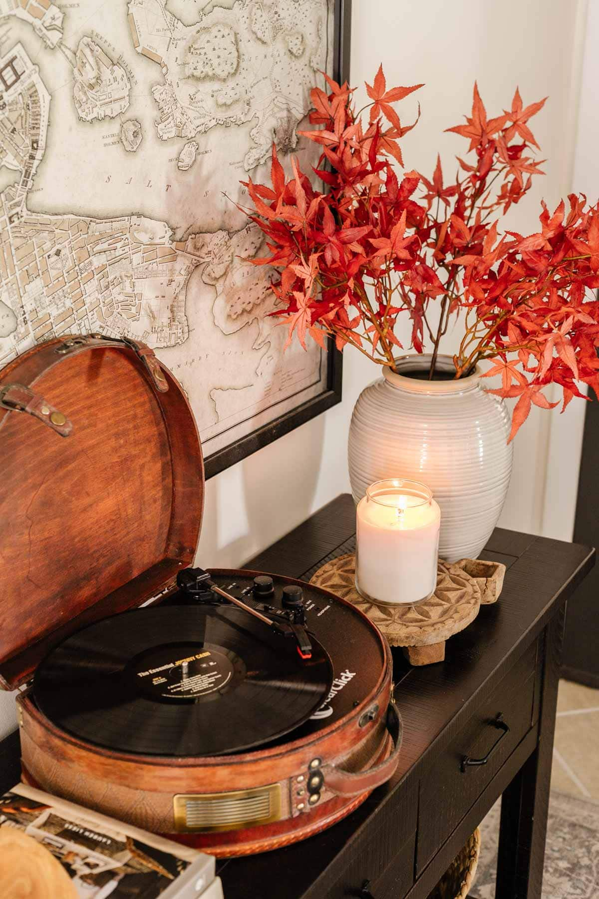 relaxing music playing on a record player with fall leaves in a vase