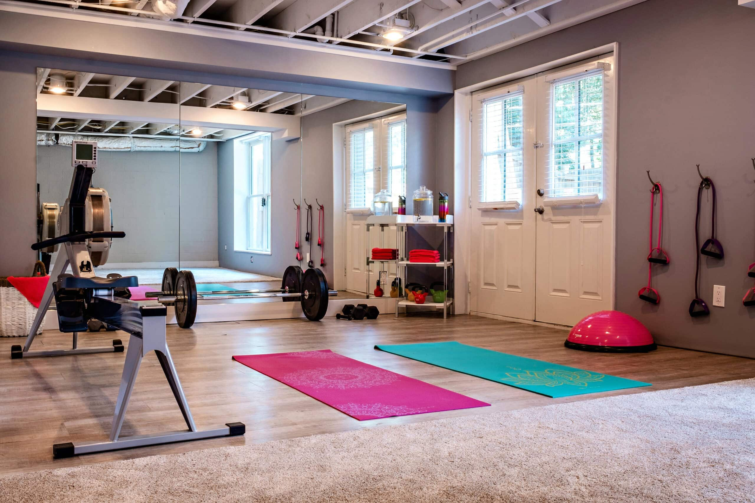 home gym with exposed ceiling and large mirrors