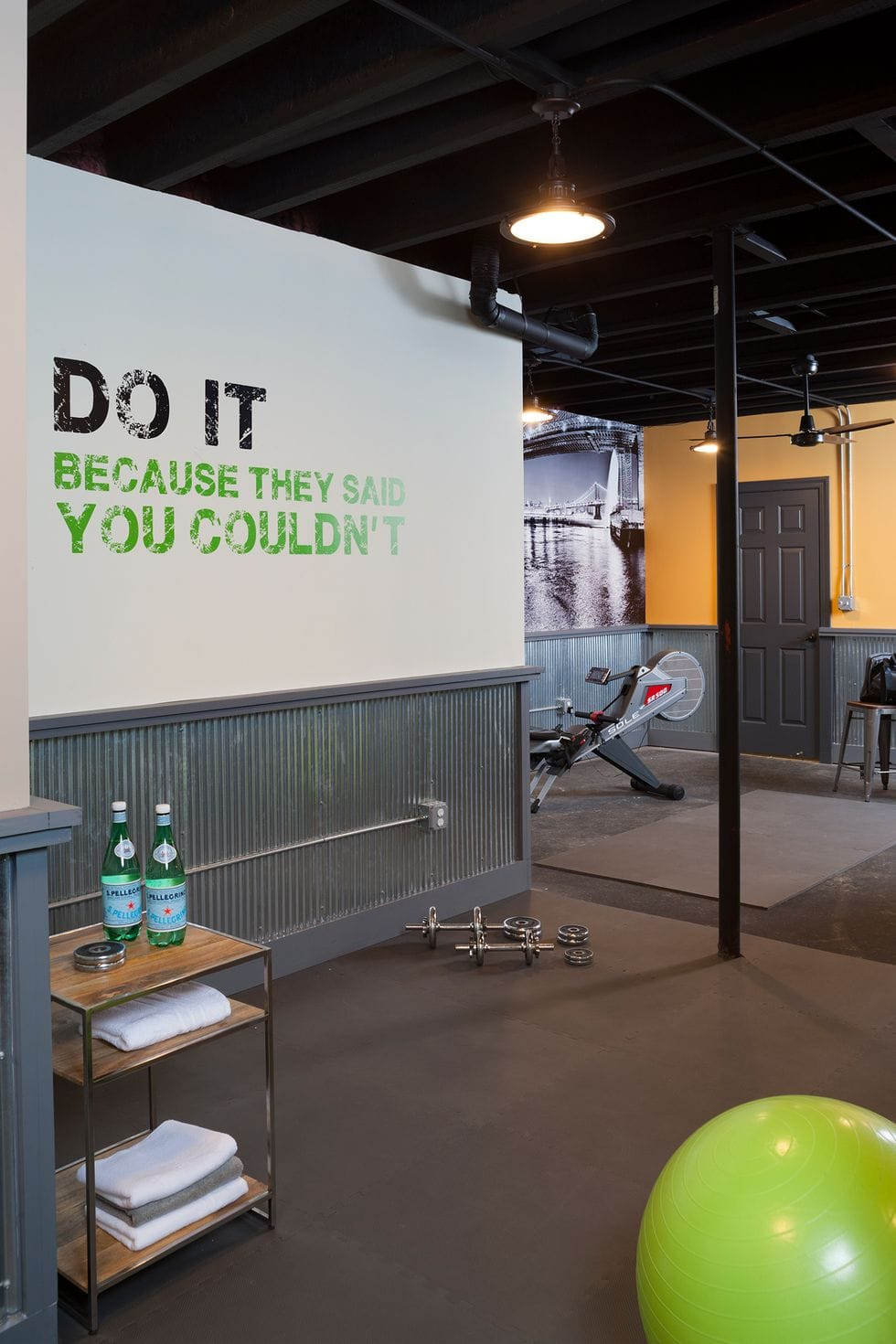 home gym with shelf, industrial lighting, and wall quote mural