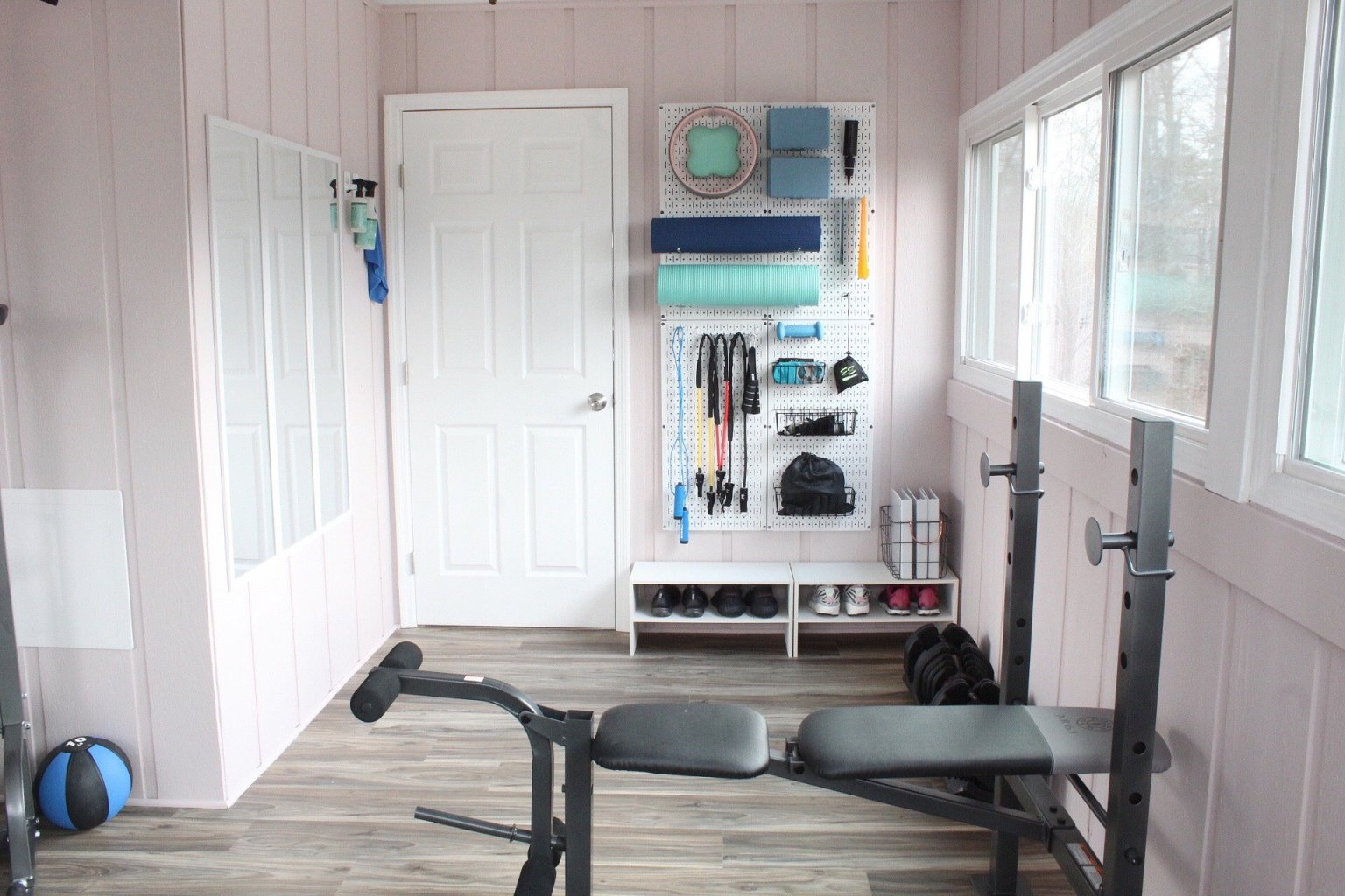 workout room with wall organizer pegboard for small workout equipment