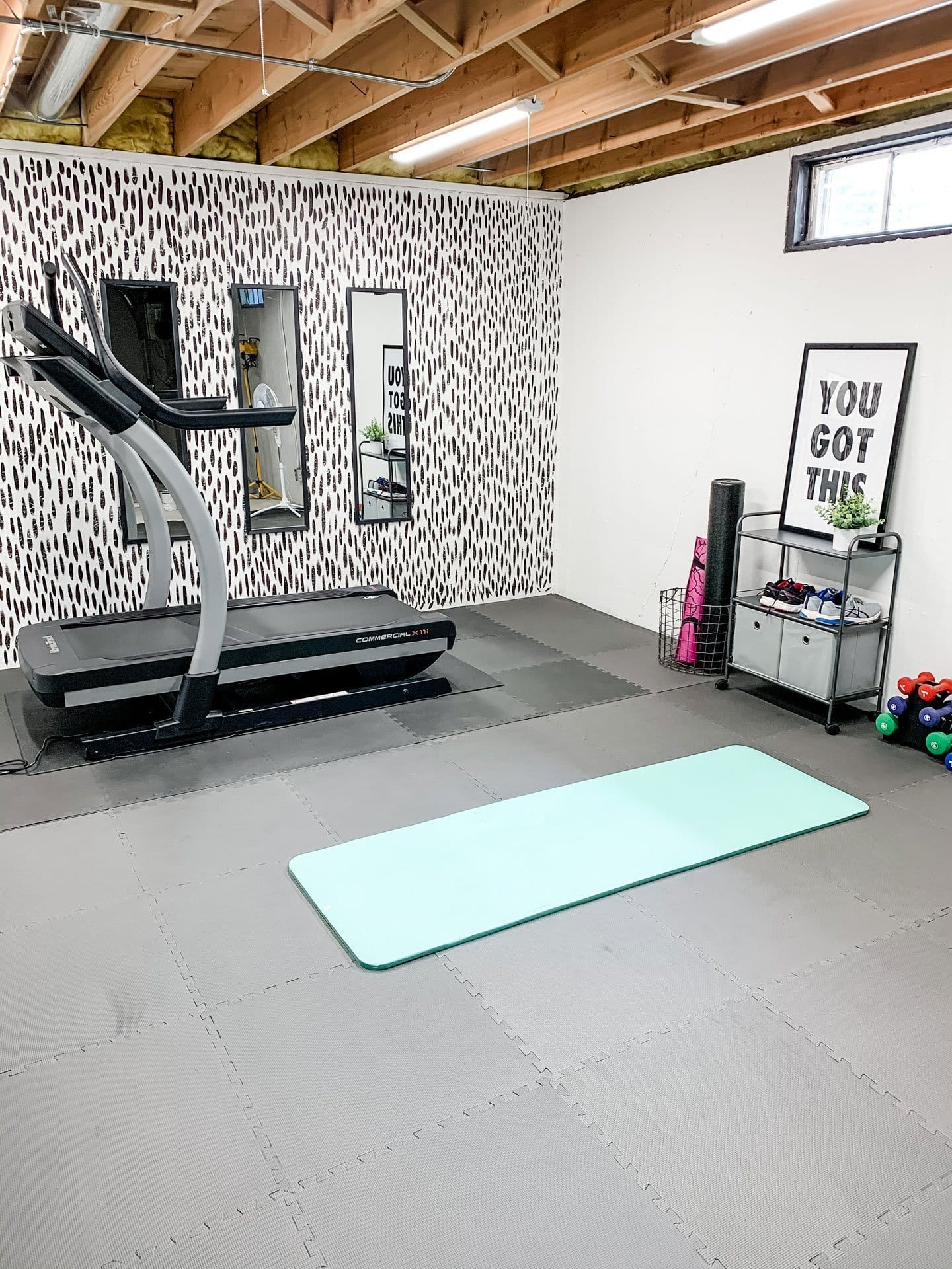 home gym with brushstroke accent wall in a basement