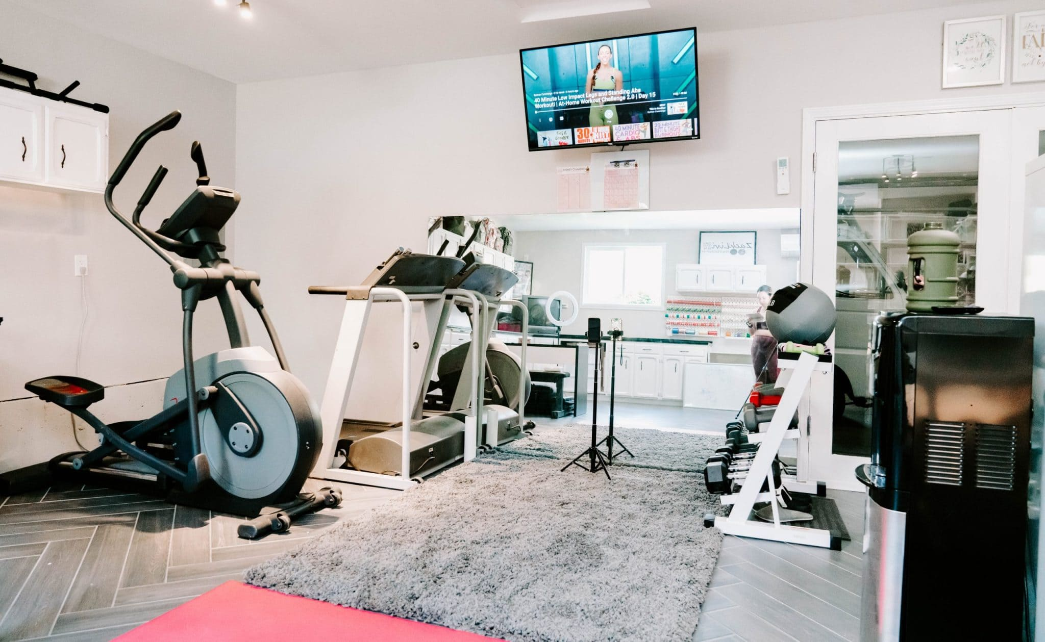 workout room with TV, large mirror, and rug