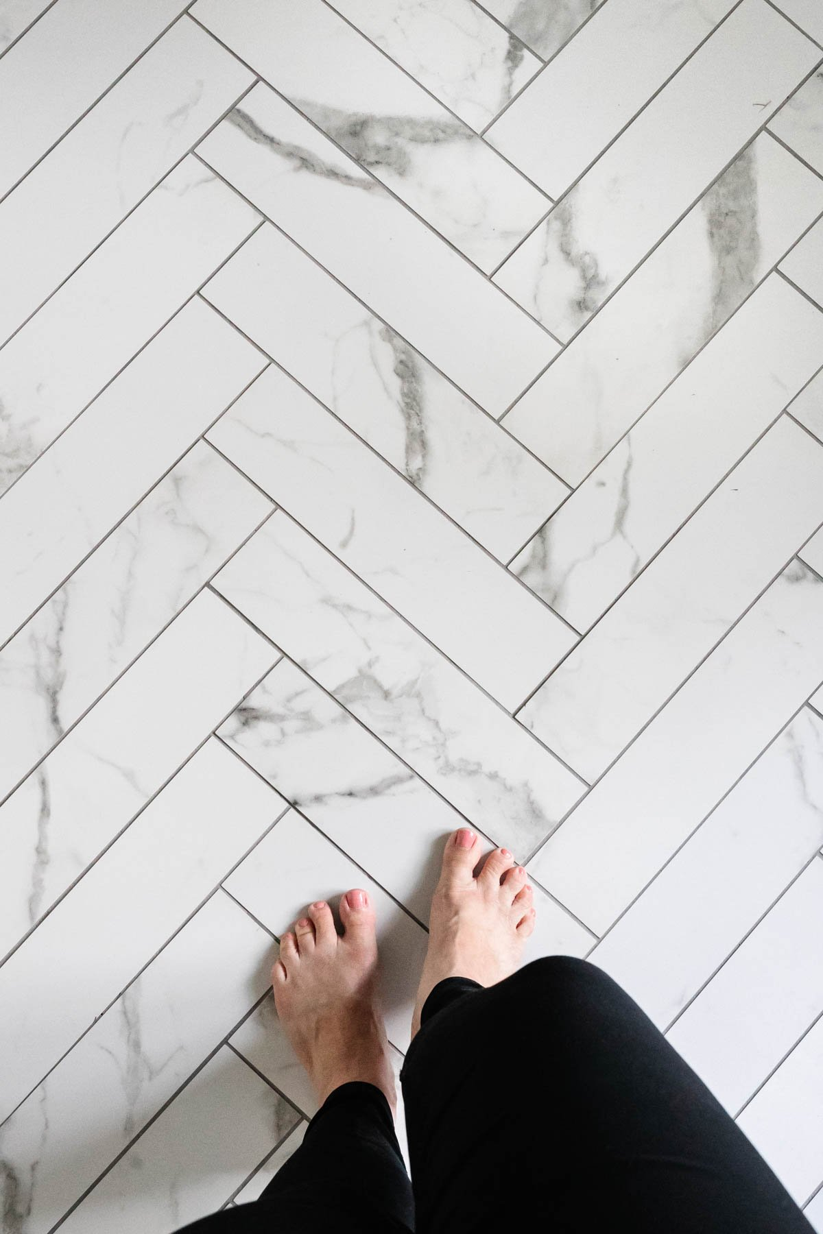 faux marble herringbone tile floor with gray grout