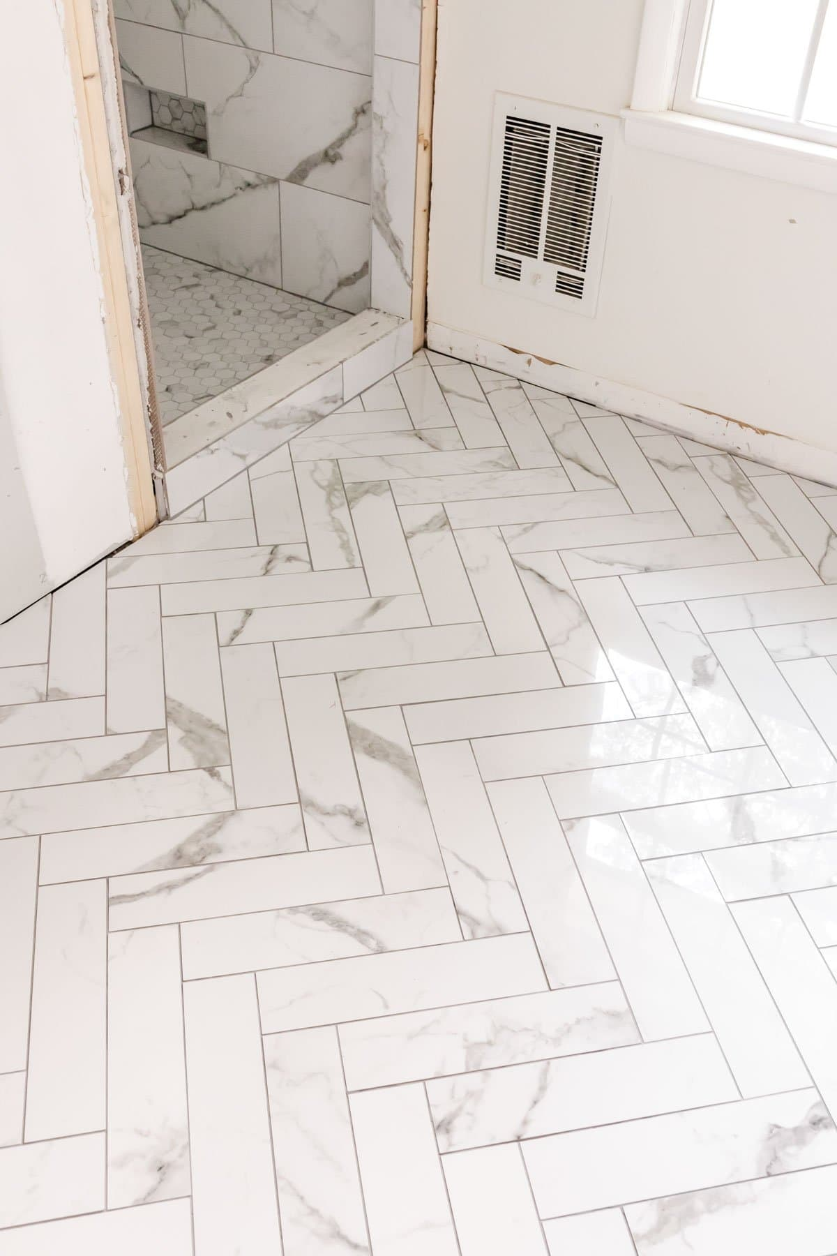 faux marble herringbone tile floor and faux marble tile shower with hexagon