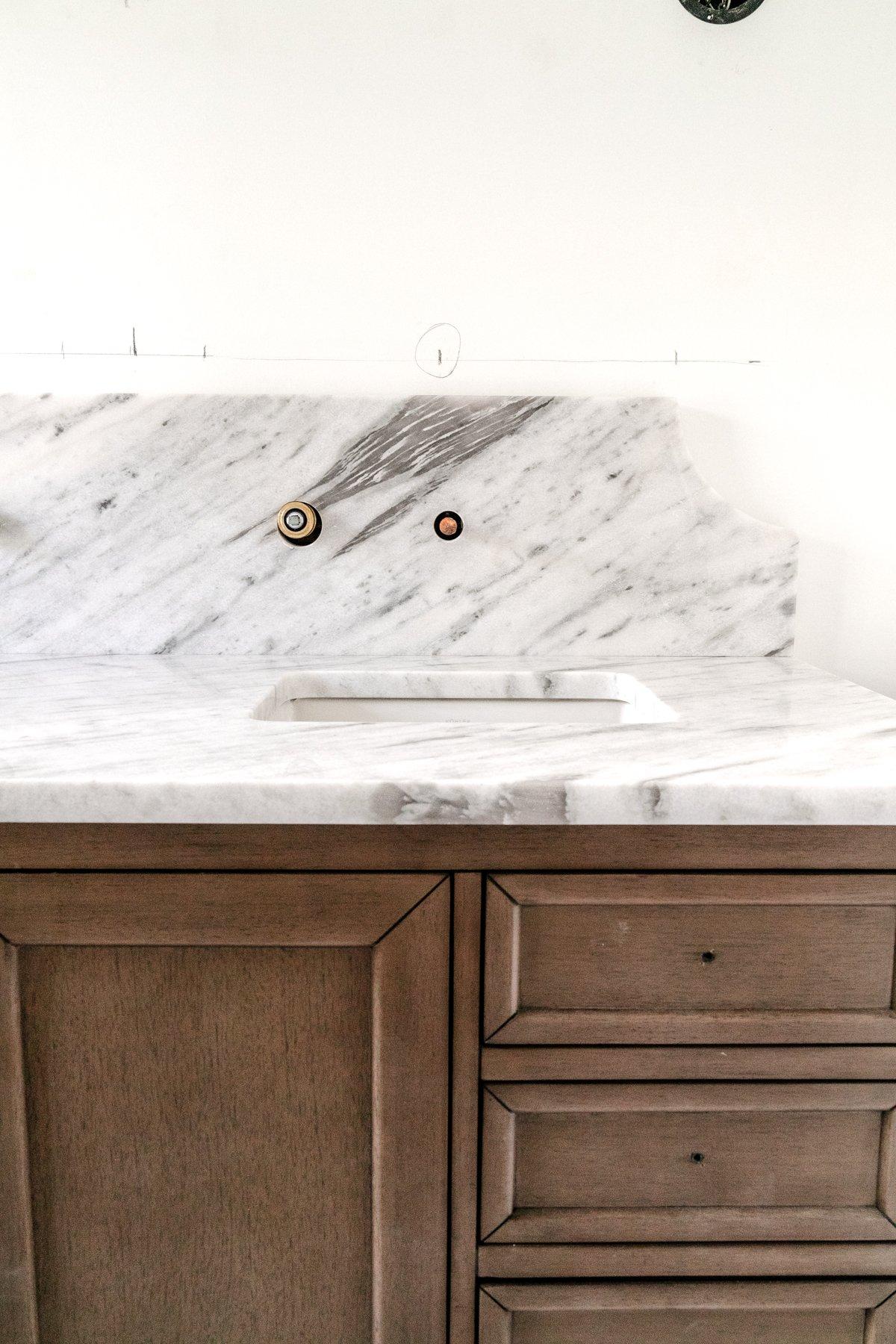 wood vanity with scalloped marble backsplash in a bathroom