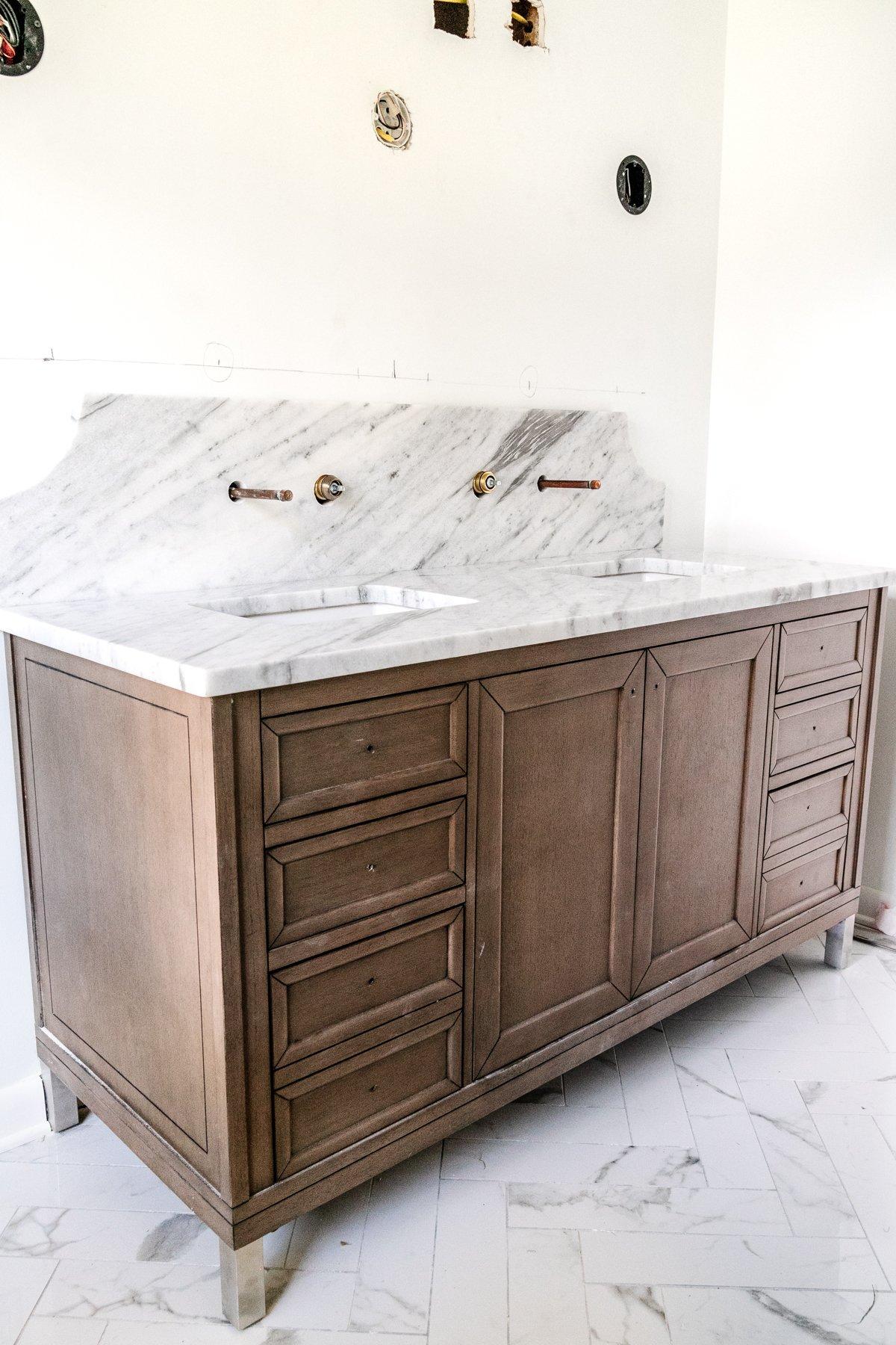 wood vanity with scalloped marble backsplash and herringbone tile