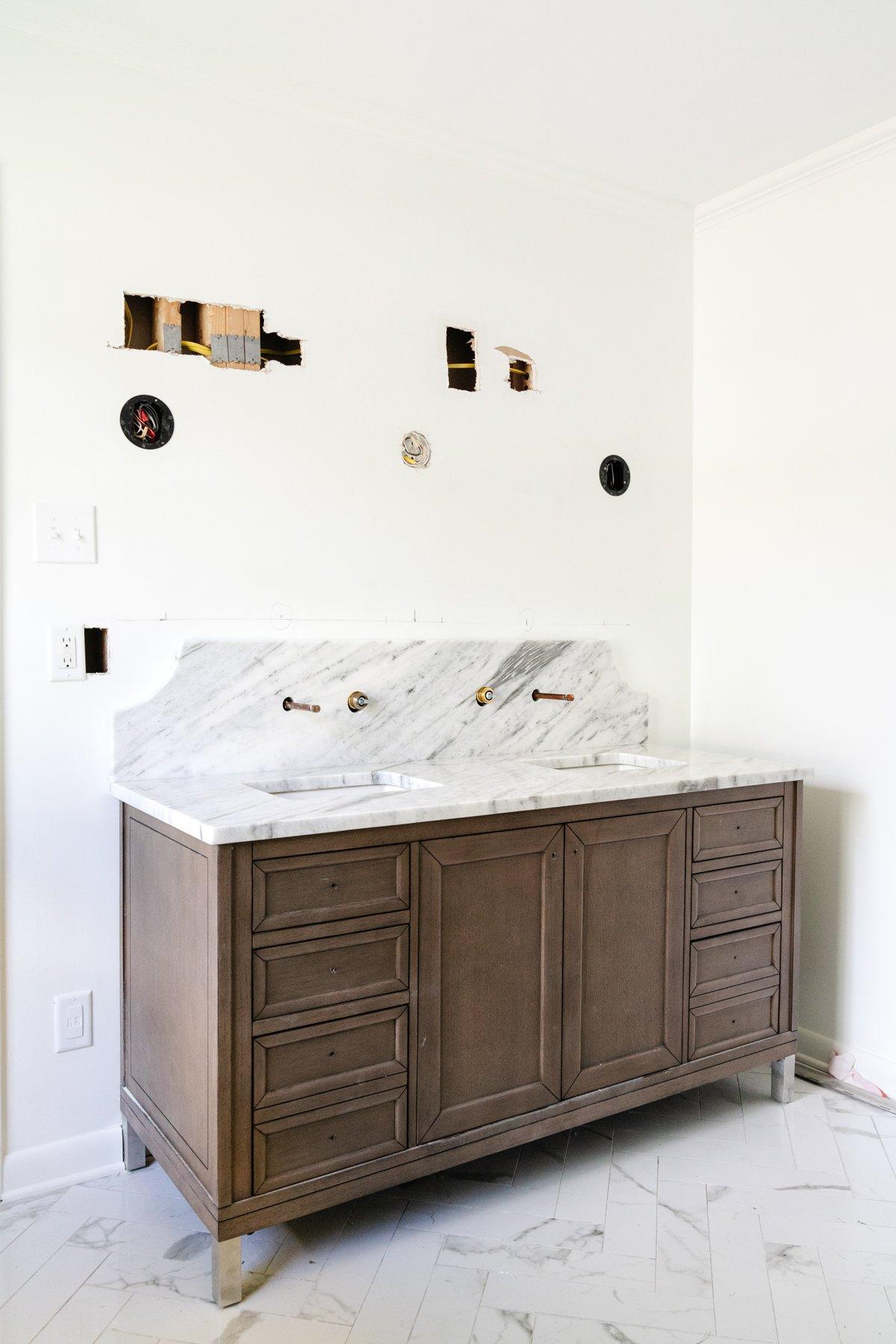 wood double vanity in a bathroom with scalloped marble backsplash and herringbone tile floor
