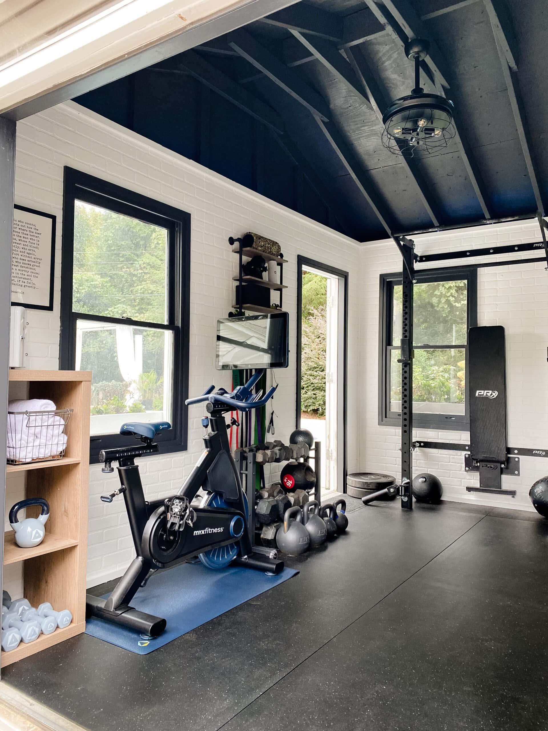 at home gym shed with cardio bike and weight lifting area