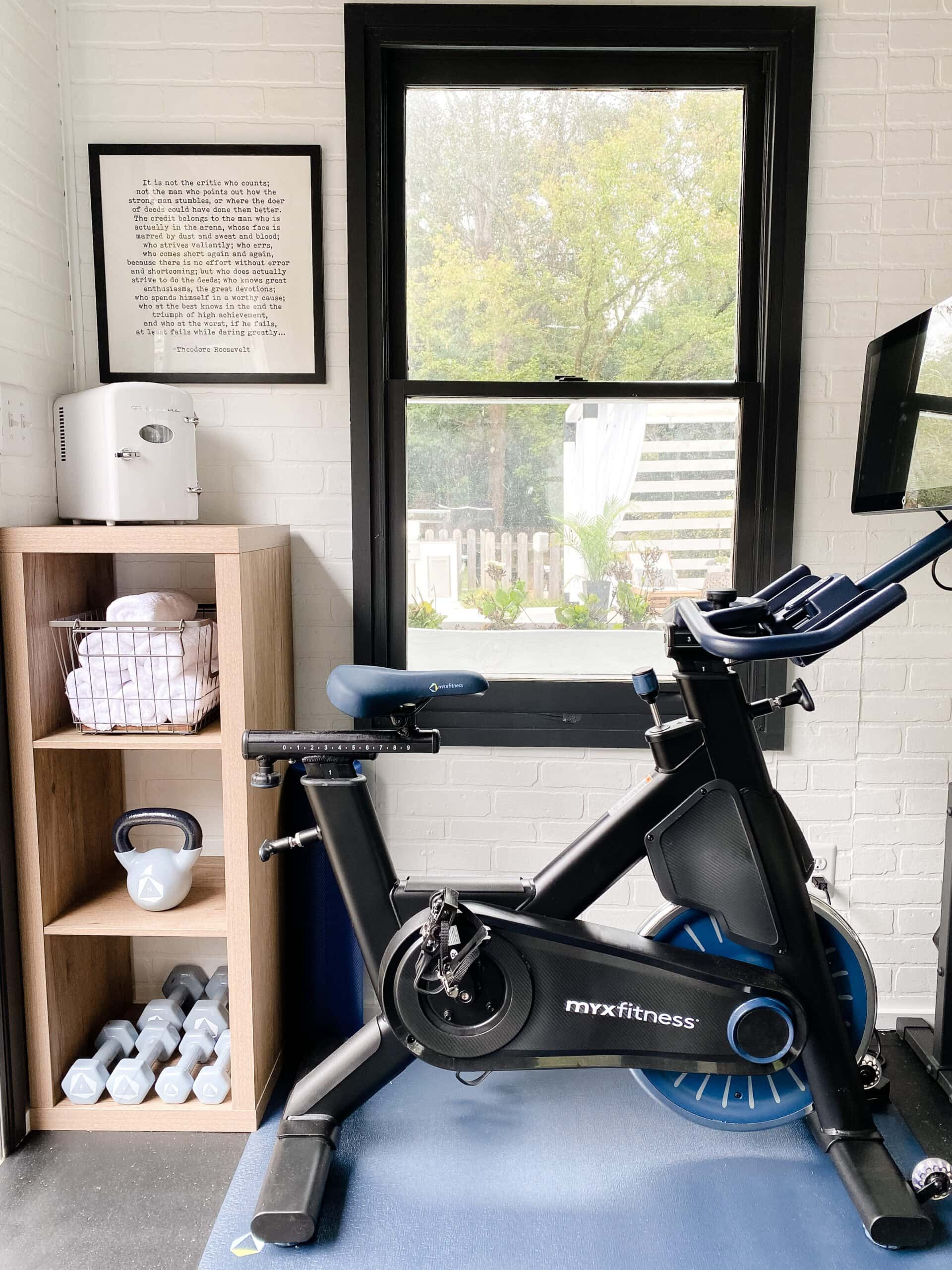 home gym shelves for storing mini fridge, hand weights, and gym towels