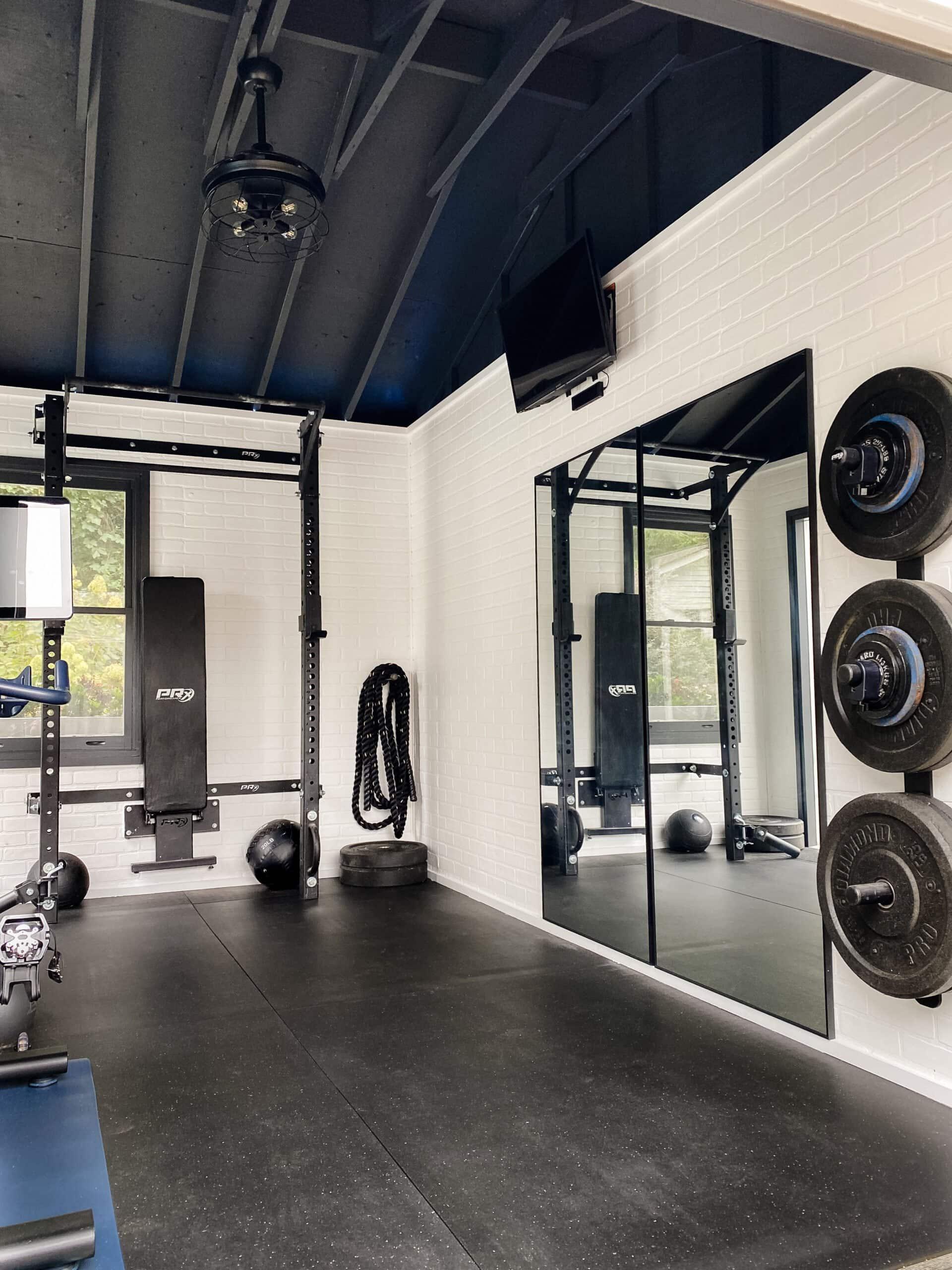at home gym shed with mirrors and faux brick walls