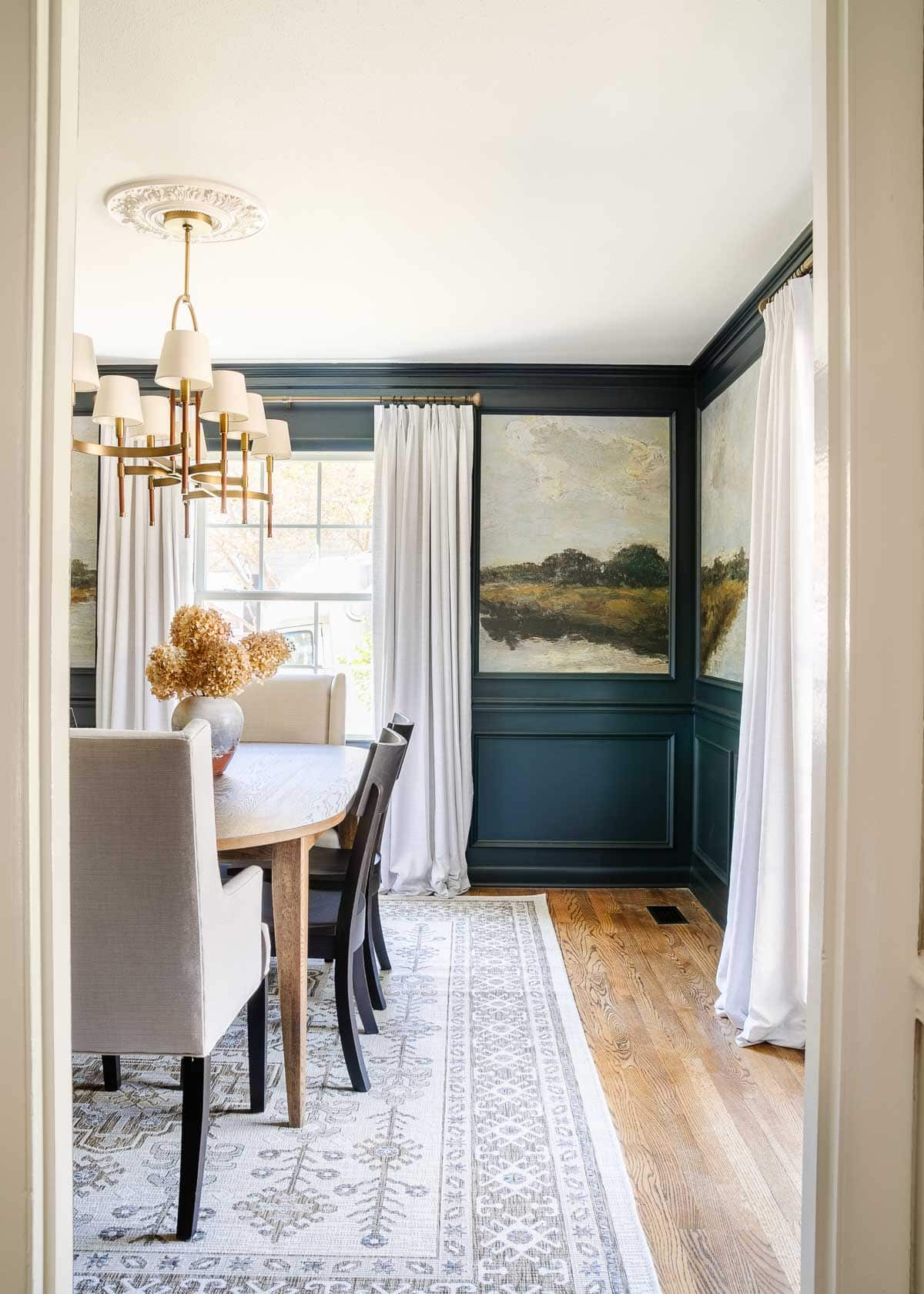 modern traditional dining room with navy blue paint, murals, and shaded chandelier